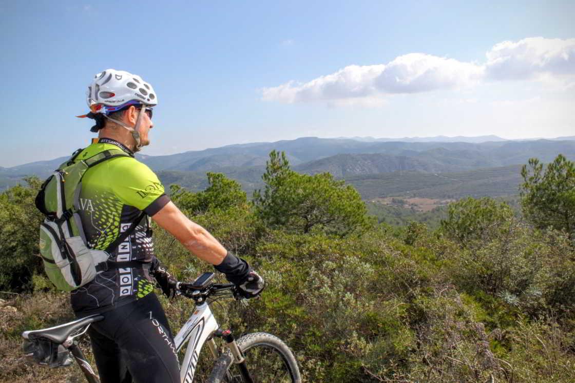 mountainbiker kijkt uit over penedès